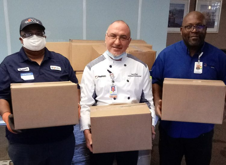 healthcare workers holding produce boxes