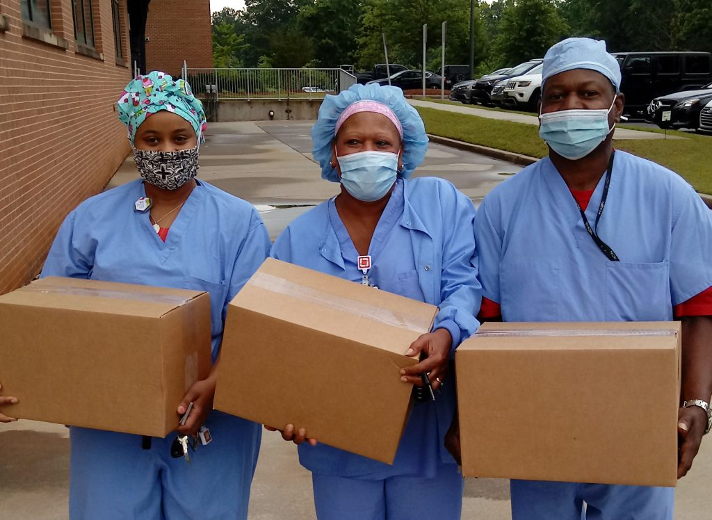 Three nurses in scrubs holding produce boxes